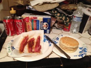 Photo of a paper plate with 3 bacon strips next to a paper plate with a stack of pancakes with a dinner knife connecting the two. There are assorted food items in the background.